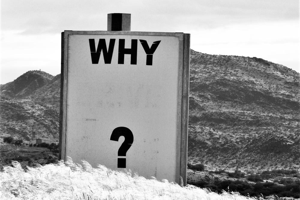 """Schild mit der Aufschrift """"why?"""""""